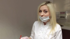 Dentist with surgical mask putting on her safety glasses in dental clinic. Stock Footage
