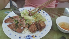Girl eating rice with pork chops Stock Footage