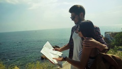 Two young people wearing sunglasses holding a map and planning new destinations Stock Footage