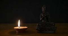 Buddha sculpture near oil candle Stock Footage