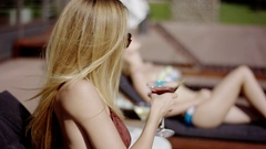 Close ups of girl taking a sip of a drink and continuing bathing sun Stock Footage