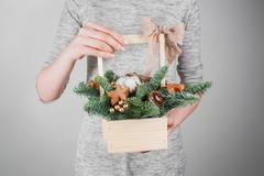 Young woman holding christmas compositionin hands in light, seasonal holidays Stock Photos