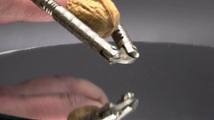 Nutcracker Crushing Walnut in Shell Reflection on Black Slow Motion Stock Footage