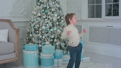 Happy little boy dancing next to the Christmas tree and presents Stock Footage