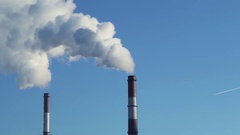 Industrial smoke from pipes against the blue sky Stock Footage
