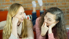 Girl looking excited while chatting with each other on the sofa Stock Footage