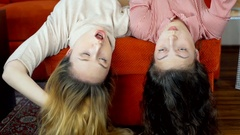 Girl talking while lying on the sofa with their heads down Stock Footage