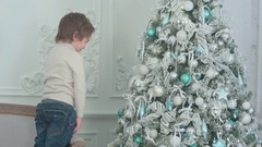 Little boy sticking his tongue out at his own reflection in the bauble on the Stock Footage