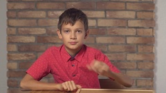 Child sitting at the desk holding flipchart with lettering jackpot on the Arkistovideo