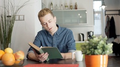 Red haired man looking absorbed while reading book and drinking coffee Stock Footage