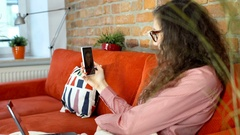 Girl sitting under blanket and chatting on smartphone with her friend Stock Footage
