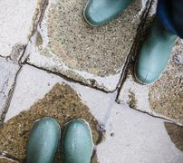 Legs in green rubber boots in puddle Stock Photos