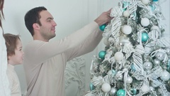 Happy parents and their son decorating Christmas tree in the living room Stock Footage