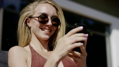 Close ups of a Young Attractive Women Relaxing with Mobile Phone in Deck Chair Stock Footage