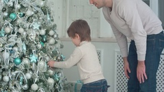 Father and son decorating Christmas tree with baubles in the living room Stock Footage