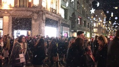 Fake snow London Oxford Circus, people Christmas shopping, at night. Stock Footage