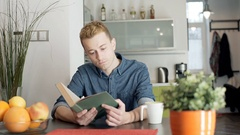 Red haired man finish reading book because of the headache Stock Footage