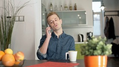 Red haired man sitting at home and having an argument while talking on cellphone Stock Footage
