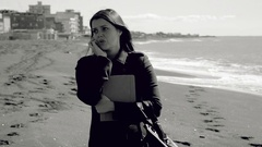 Angry business woman on the beach talking on the phone black and white Stock Footage