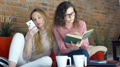 Girl browsing internet on smartphone while her friend is reading book Stock Footage