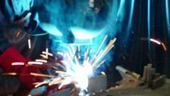 Welder Welds in a Metal Industry in blurred scene Stock Footage