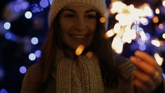 Woman in winter enjoying with a sparkler outdoors in an urban square Stock Footage