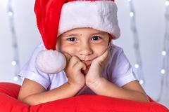 A small child dressed as Santa Claus in anticipation of Christmas and New Year Stock Photos