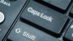 Extreme close up of a finger pressing 'caps lock' on a keyboard Stock Footage