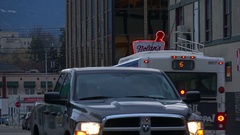 Smalltown traffic neon pharmacy sign, transit bus at dusk Vernon BC Stock Footage