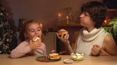 Mother and daughter eating cinnamon rolls Stock Footage