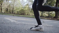 Closeup, slow motion shot of feet running on pavement Stock Footage