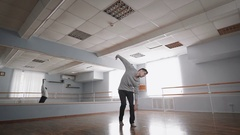 Young man in grey pullover dancing modern dance in the ballroom with barre Stock Footage