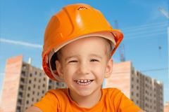 Portrait of a child in the construction helmet on a background of high-rise buil Stock Photos