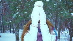 Girl in warm winter clothes smiles on camera in a winter forest Stock Footage