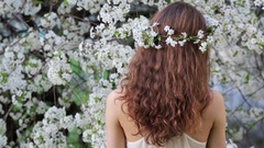 Young woman enjoying smell of blooming tree Stock Footage