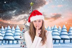 Woman in santa hat with finger on lips against digitally generated background Stock Photos