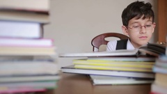 Boy sitting at a table with a stack of books. child reading. boy with glasses Stock Footage