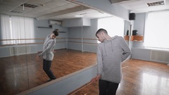Young student of dancing school standing near the mirror and showing knowledge Stock Footage