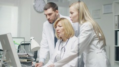 Medical Personnel Discuss Work Related Issues while Using Personal Computer.  Stock Footage