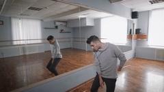 Dancer is dancing near the mirror. Light dance class with a window. Dance Stock Footage