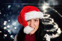 Frustrated woman biting santa hat Stock Photos