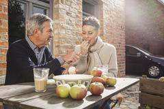Mature couple eating apples in back yard Stock Photos