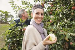 Portrait of happy woman eating apple in orchard Stock Photos