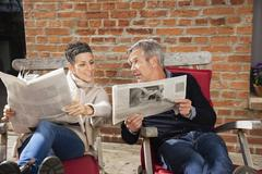 Man showing newspaper to happy woman while sitting in back yard Stock Photos