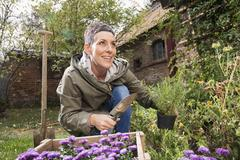 Happy woman holding trowel and pot plant in back yard Stock Photos