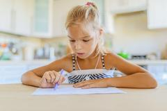 Little girl writing with pen in notebook Stock Photos