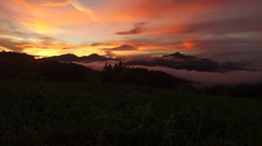 Intensive bold colors of sunset over foggy forests and mountains Stock Footage