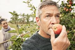 Man smelling fresh apple in orchard Stock Photos