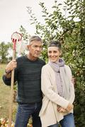 Portrait of happy woman standing with man in apple orchard Stock Photos