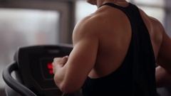 Back and side view of a strong bodybuilder running on a treadmill while working Stock Footage